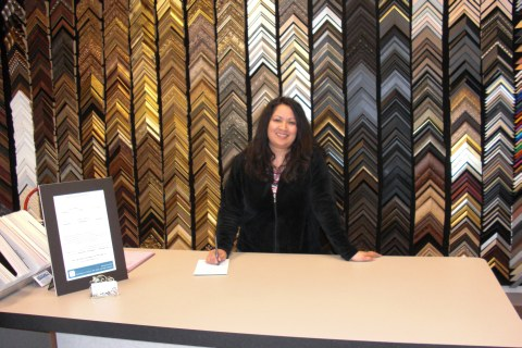 An employee standing behind a work table and in front of a display of moulding corner samples